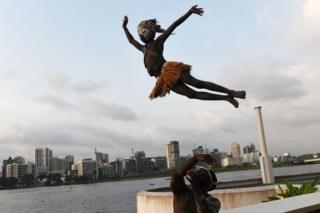 """A man throws a child in the air before an international traditional dance competition on December 9, 2016 at the Palais de la Culture d""""Abidjan."""