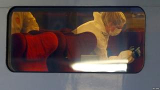 French investigating police in protective clothing films inside the Thalys high-speed train where shots were fired in Arras, France (21 August 2015)