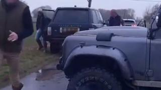 Three men getting out of off-road vehicles