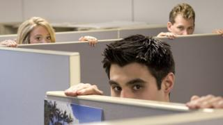 Businesspeople peering over cubicle walls