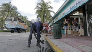 A Miami-Dade mosquito control inspector sprays a chemical mist into a storm drain.