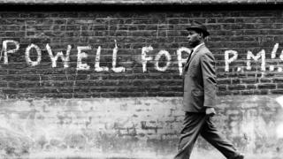 """Man walking past graffiti stating """"Powell For PM"""" (prime minister), 1st May 1968"""