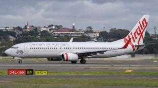 A Virgin Australia Boeing 737-800 series aircraft on the runway at Sydney's main international airport.