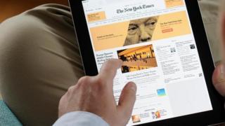 Homem vê página do The New York Times em tela de tablet