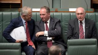 Australian Prime Minister Malcolm Turnbull (L) speaks to Australian Agriculture Minister Barnaby Joyce (C) as Federal Minister for Infrastructure and Regional Development Warren Truss sits next to them in the House of Representatives at Parliament House in Canberra, Australia, February 11, 2016