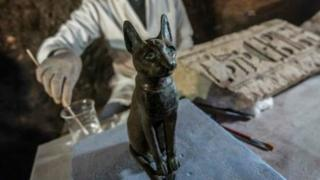 一名埃及考古學家為貓女神的青銅雕像清理