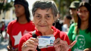 Una señora sujeta su carnet de la patria.