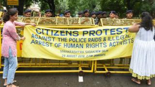 Delhi Police personnel stand on duty as people stage a protest against the arrest of five activists