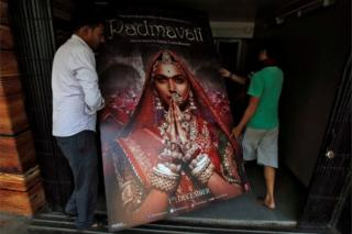 """Workers carry a poster advertising upcoming Bollywood film """"Padmavati"""" towards a ticket selling counter in a cinema hall in Kolkata, India, November 28, 2017."""