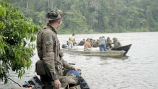 Militar observa homens sendo revistados em barco no meio da floresta