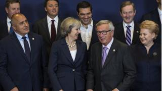 Theresa May alongside Jean-Claude Juncker during the summit group photo