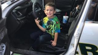 Young Billy sits in the patrol car on Thanksgiving day.