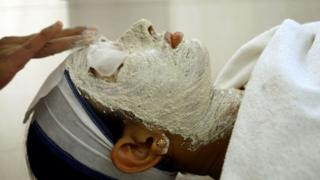 An Indian woman receives a facial at a beauty salon in New Delhi