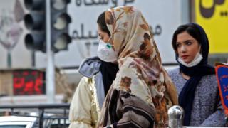 A woman wearing a face mask walks on a street in Tehran, Iran (24 February 2020)