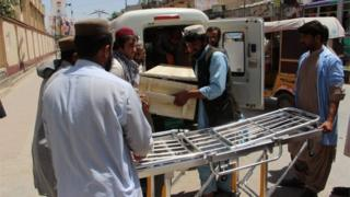 People shift a coffin containing body of one of the two people killed in a US drone in Noshki, and one of the said to be of Taliban leader Mullah Akhtar Mansoor, after the bodies were brought to a hospital in Quetta, Pakistan, 22 May 2016.