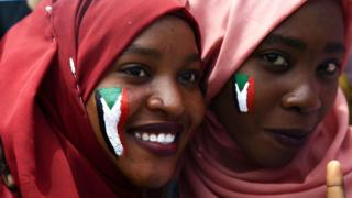 Sudanese women with national flags painted on their faces take part in a rally.