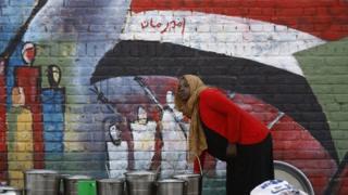 فتاة ترسم على أحد الجدران علم بلادها
