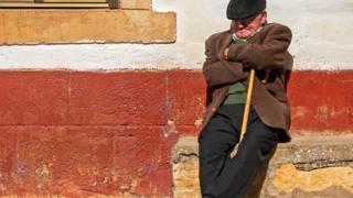 رجل أسباني يأخذ قسطا من الراحة أو غفوة وهو يجلس بجوار أحد المنازل