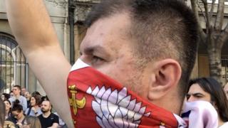 Jedan od demonstranata na protestu nosi zastavu Srbija kao maramu preko lica