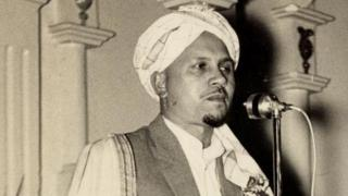 Portrait en noir et blanc de l'imam Haron s'adressant à un auditoire avec un microphon