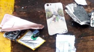Damaged phone and phone case showing a couple walking across a bridge