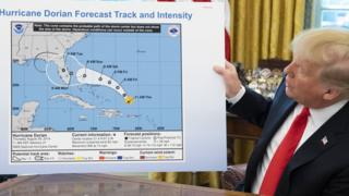 US President Donald Trump holds up a NOAA map of a previously projected path of Hurricane Dorian