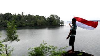Anselmus mengibarkan bendera Indonesia