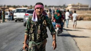 A Syrian regime soldier patrols a street