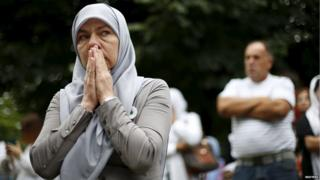 A woman reacts as she stands near a truck carrying 136 coffins of newly identified victims of the 1995 Srebrenica massacre, in the village of Visoko,Bosnia and Herzegovina, July 9, 2015.