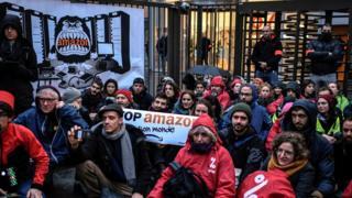 """نشكاء محتجّون على """"الجمعة السوداء"""" يغلقون مدخل المقر الرئيسي لشركة أمازون في فرنسا رافعين لافتة كتب عليها"""" أوقفوا أمازون وعالمها""""."""