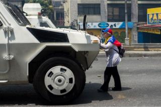 A woman stands in front of a vehicle of the Venezuelan security forces on 19 April 2017