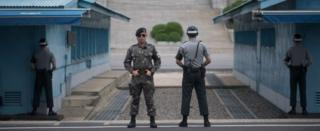 South Korean soldiers stand guard before North Korea's Panmon Hall (rear C) and the military demarcation line separating North and South Korea, at Panmunjom, on 6 August
