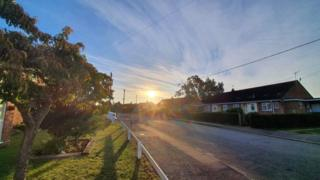 Sun rises over houses in Harleston
