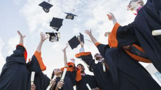 Stock picture of university graduates throwing mortar boards in the air