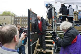 Tony Benn walking down steps after being interviewed