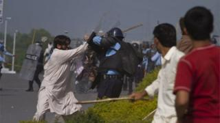 A Pakistani protestor scuffles with a police officer during clashes that erupted as the demonstrators tried to approach the U.S. embassy in Islamabad, Pakistan, Friday, Sept. 21, 2012.