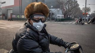 A man wearing a protective face mask and goggles rides on a vehicle in Beijing, China, 11 February 2020.