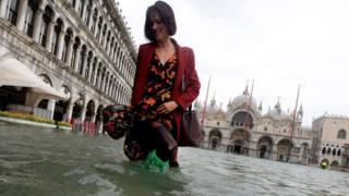 Tourist in flooded water in Venice on 29 October 2018