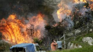 Two neighbours look at the flames as firefighters work to extinguish a forest fire at Ribera de Arriba in Asturias
