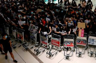 Anti-extradition bill protesters use trolleys to stop passengers from entering the security gates during a mass demonstration after a woman was shot in the eye, at the Hong Kong international airport, in Hong Kong China