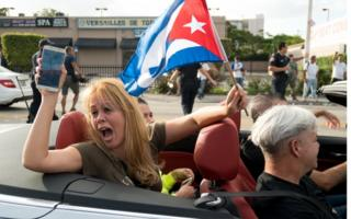 People react to news of the death of former Cuban President Fidel Castro outside the restaurant Versailles 26 November 2016 in Miami, Florida. Many, mostly Cubans, gathered to wave flags and celebrate the news of the death of the Cuban revolutionary