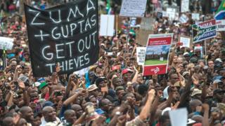 "Protester hold banner saying ""Zuma and Guptas Get Out Thieves"""