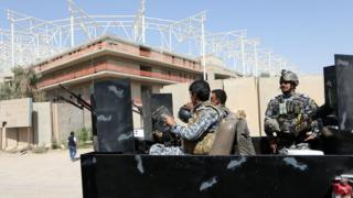 Iraqi security forces guard the entrance to a sports stadium under construction in Baghdad's Sadr City district (2 September 2015)