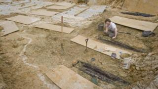 researchers unearthing coffins
