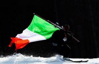 An Italian coach carries the national flag