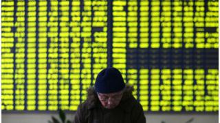 A stock investor pauses near a display board showing stock prices in green to symbolize a fall in price, at a brokerage house in Jiujiang on Monday