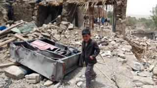 A young boy walking through rubble in Yemen
