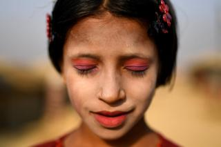 Rohingya refugee Amina poses for a photograph as she wears thanaka paste at Kutupalong camp in Cox's Bazaar, Bangladesh