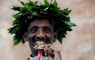 Ethiopia's Tebalu Zawude Heyi bites the winner's medal as he celebrates on the podium after winning the 25th edition of the men's Rome Marathon in Rome, Italy - Sunday 7 April 2019