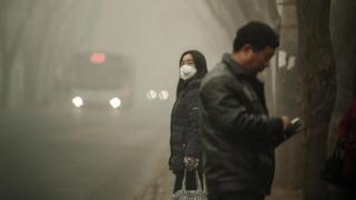 بعض الأشخاص في الصين يرتدون أقنعة لعدم استنشاق الهواء الملوث